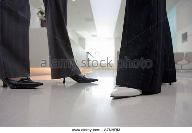 Two businesswomen wearing high heels and trousers talking in lobby side view low section surface level - Stock Image