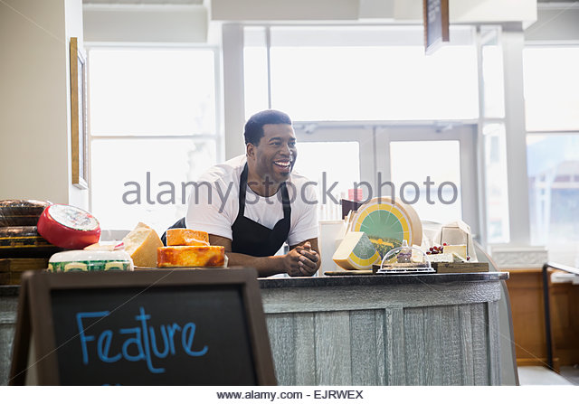 Smiling business owner at cheese counter - Stock Image