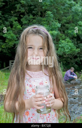 Girl with jam jar by the river - Stock Image