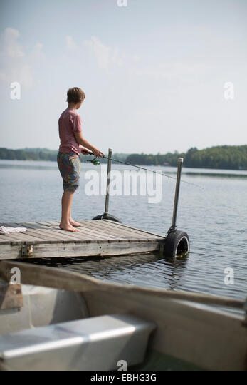 Teenage boy fishing on pier, Lake Superior, Gwinn, Michigan, USA - Stock Image