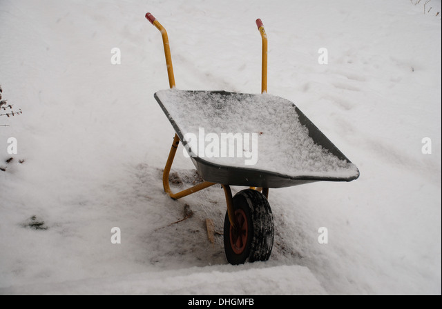 wheelbarrow in the snow - Stock Image