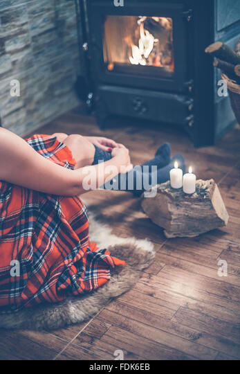 Woman sitting in front of a wood burning stove and candles - Stock Image