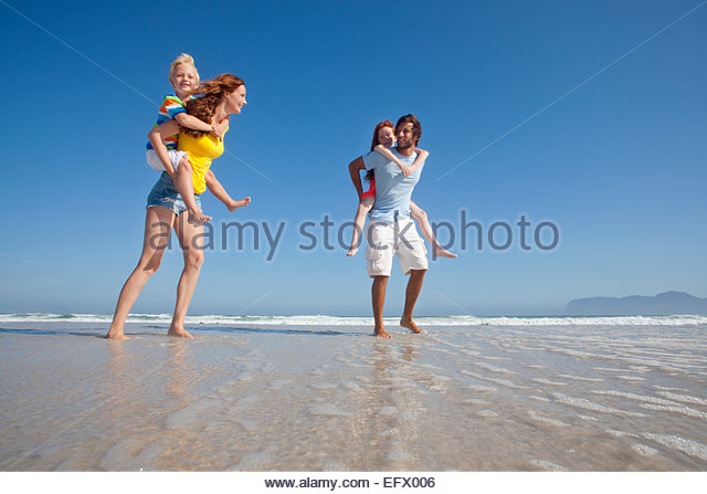 Mother and father, giving two children piggy back, whilst paddling in sea on sunny beach - Stock Image