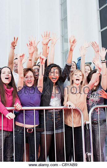 Fans waving from behind barrier - Stock-Bilder