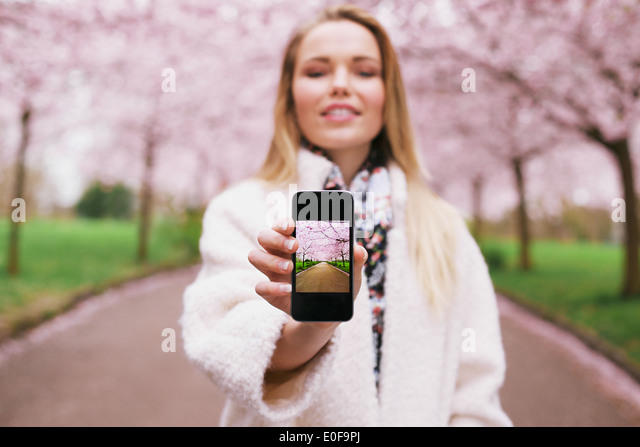 Young woman showing a photograph on her smart phone at you. Female at spring park displaying images on her mobile - Stock Image