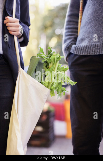 Cropped image of couple with groceries outdoors - Stock Image