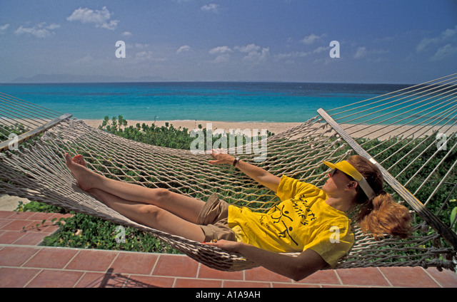 Caribbean beach resort with single woman alone in hammock - Stock Image