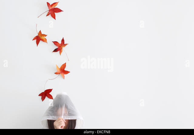 Autumn leaves falling on a mid adult woman wearing a raincoat - Stock-Bilder