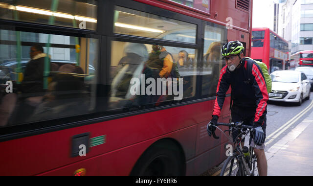 Cyclist with anti pollution smog mask, pushed off road by bus, on City of London street - Stock Image