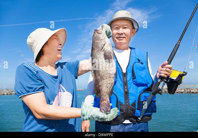happy asian senior couple fishing and showing big grouper - Stock Image