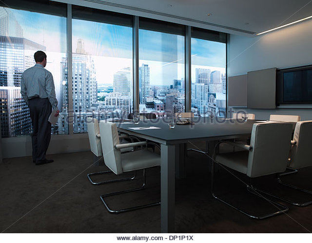 Businessman standing at conference room window overlooking city - Stock Image