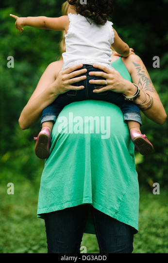 Pregnant Woman Holding Young Child on Belly - Stock Image