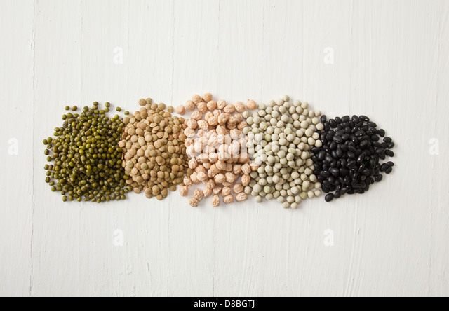 Piles of peas, beans, lentils, sprouts and pulses in a line on a rustic wood surface. - Stock Image