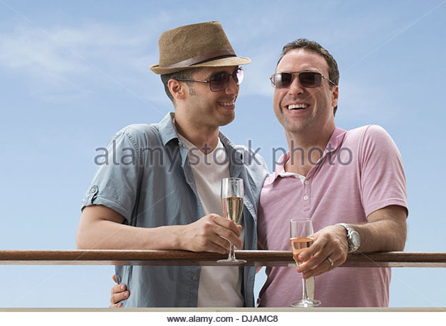 Gay couple having champagne on cruise ship - Stock Image