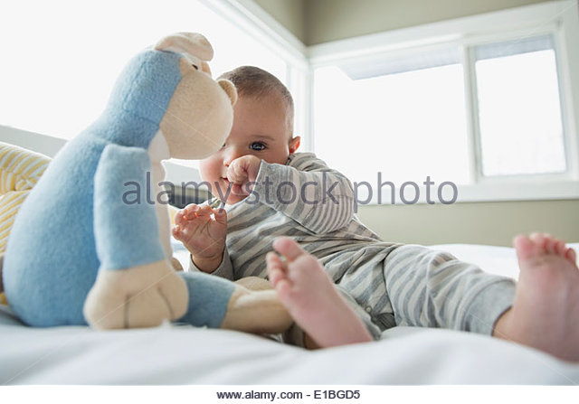 Baby with stuffed animal on bed - Stock-Bilder