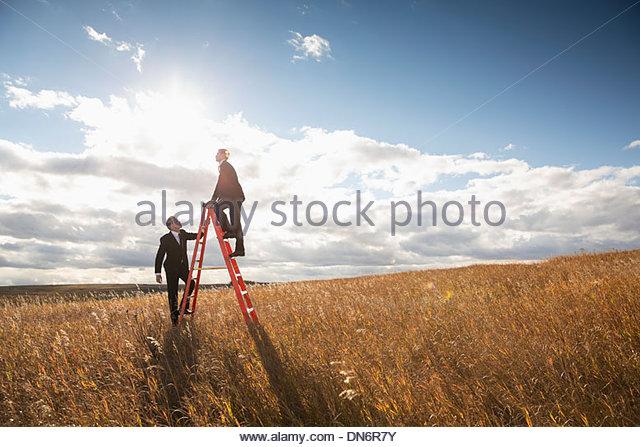 Businessmen climbing step ladder on field - Stock Image