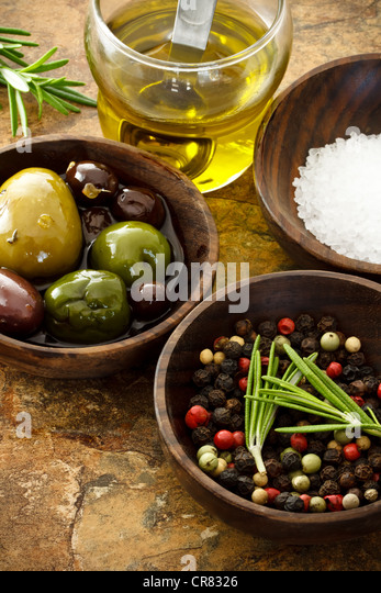 Olive oil, peppercorn, sea salt on stone table - Stock Image