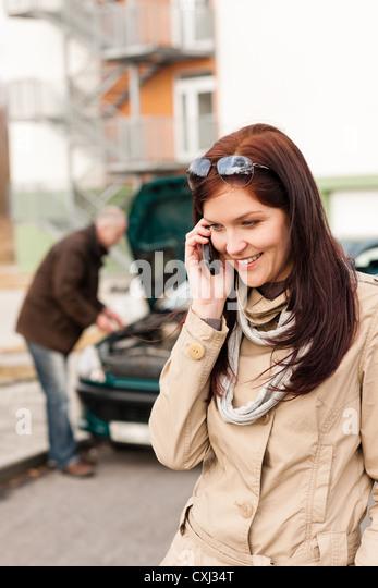 Woman on the phone repairman fixing car breakdown crash problem - Stock Image