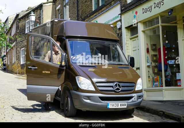 Ups van and driver delivering goods on the narrow cobbled streets of Haworth, West Yorkshire, England,UK. - Stock Image