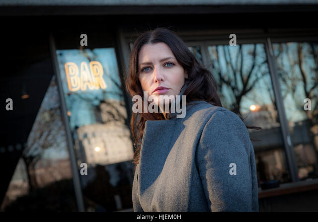 Attractive dark haired woman looking to camera, outside a bar - Stock Image