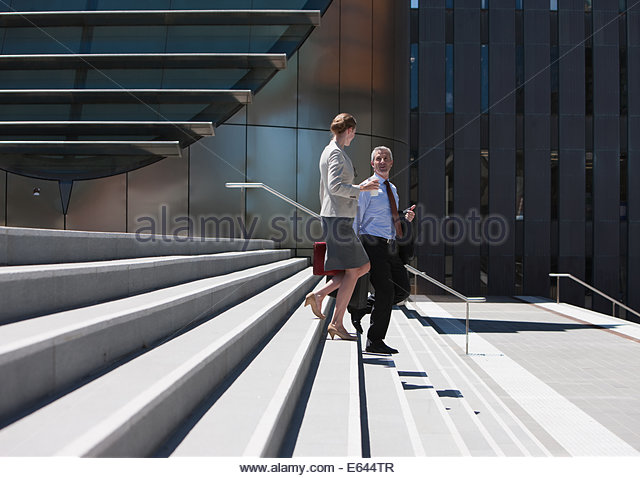 Business people walking down steps - Stock Image