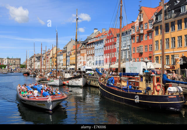 Tourists on Copenhagen canal tour boat with old boats moored in front of colourful buildings. Nyhavn Copenhagen - Stock Image