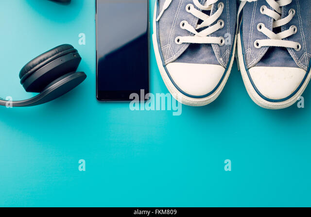 headphones, smart phone and sneakers on colorful background - Stock-Bilder