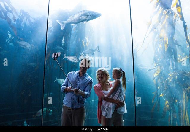 Happy family using selfie stick - Stock-Bilder