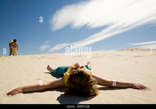 Image of restful boy lying on sand under blue sky and enjoying sunny day - Stock Image