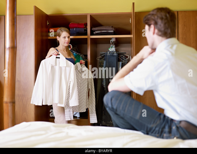 caucasian couple getting dressed in the morning, with woman choosing shirt. Horizontal shape, front view, three - Stock Image