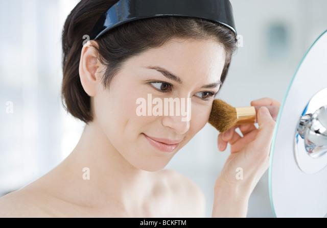 Young woman applying make up - Stock Image