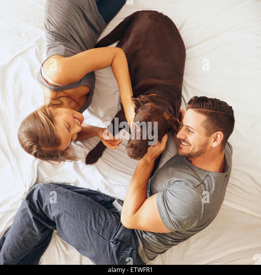 Top view of happy young family relaxing on bed together. Man and woman with pet dog in bedroom. - Stock Image