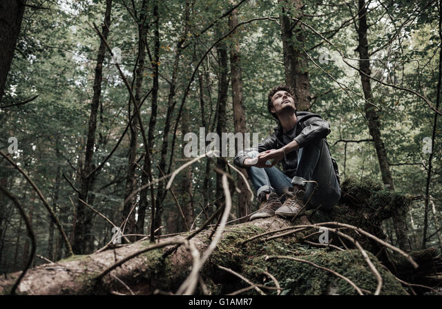 Young man sitting on a trunk in the forest and relaxing, freedom and individuality concept - Stock Image
