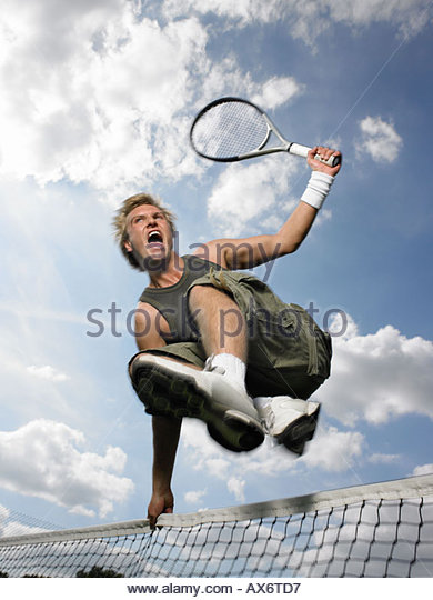 Man jumping over tennis net - Stock Image