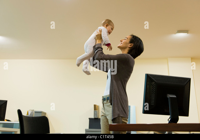 Mother playing with baby in office - Stock Image