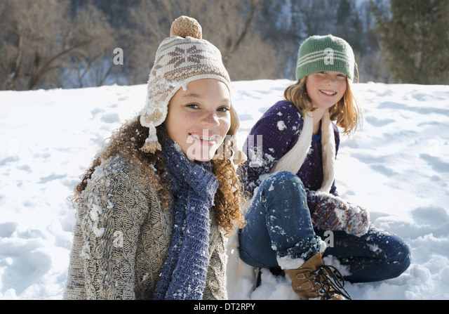 Winter scenery with snow on the ground A woman and a child sitting on the ground laughing - Stock Image