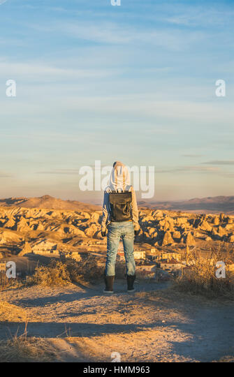 Young woman traveller standing and watching sunrise, Cappadocia, Central Turkey - Stock Image