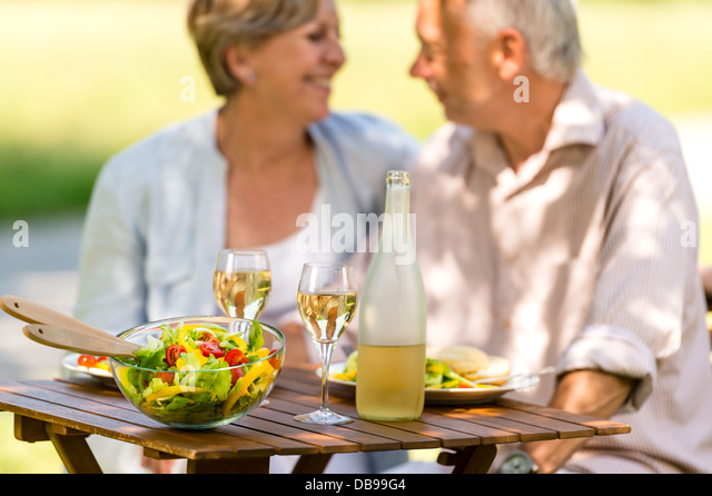 Cheerful senior citizens dating and eating outdoors - Stock Image