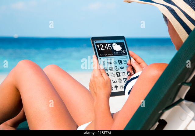 Woman on vacation lies in a sun lounger on the beach with a tablet in hands. - Stock Image
