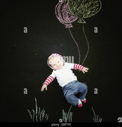 Baby boy (18-23 months) with chalk drawing of balloons - Stock-Bilder