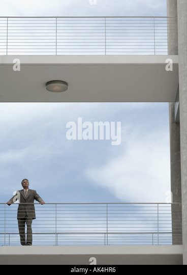 Businessman standing on walkway with hands on railing, looking into distance - Stock Image