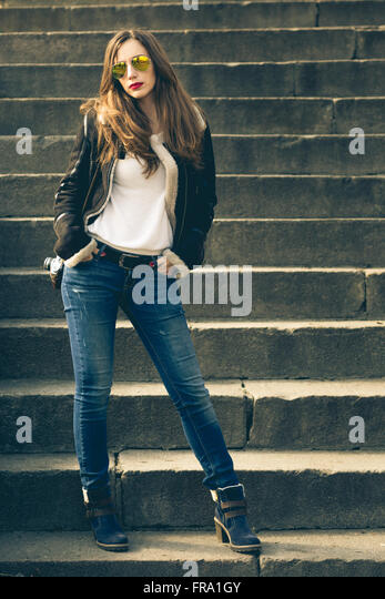 Young fashion woman with photo camera stands on the stairs. Attractive stylish caucasian girl in city outdoors - Stock Image