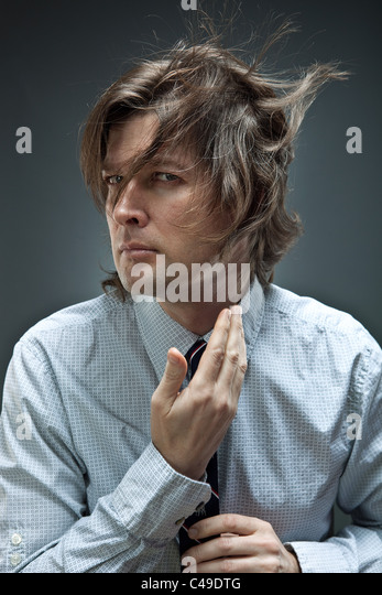 Studio shot of man in button-down oxford shirt adjusts his cuffs while his brown hair blows around. - Stock Image