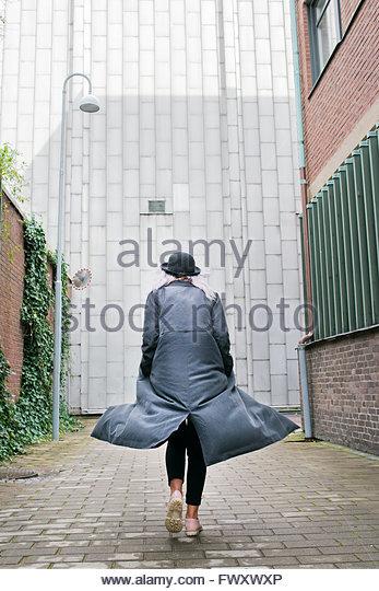 Sweden, Vastra Gotaland, Young woman wearing long overcoat walking away - Stock-Bilder