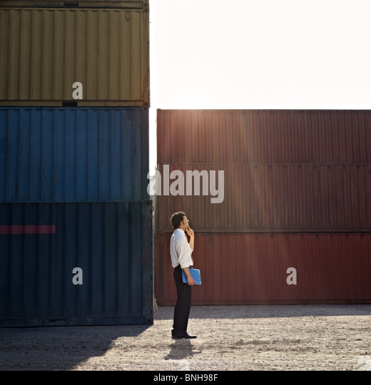 mid adult businessman standing near cargo container and looking up. - Stock Image