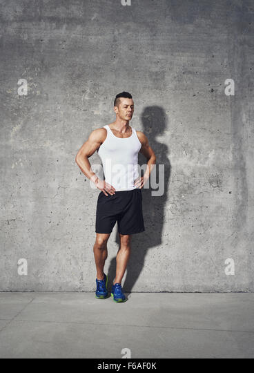 Full body fitness portrait of muscular man, standing with both hands on his waist looking away - Stock Image