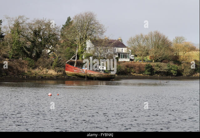 House and derelict trawler on the River Lennon at Ramelton. - Stock Image