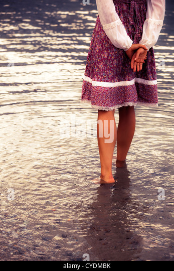 a girl in a vintage dress is standing in the water - Stock Image