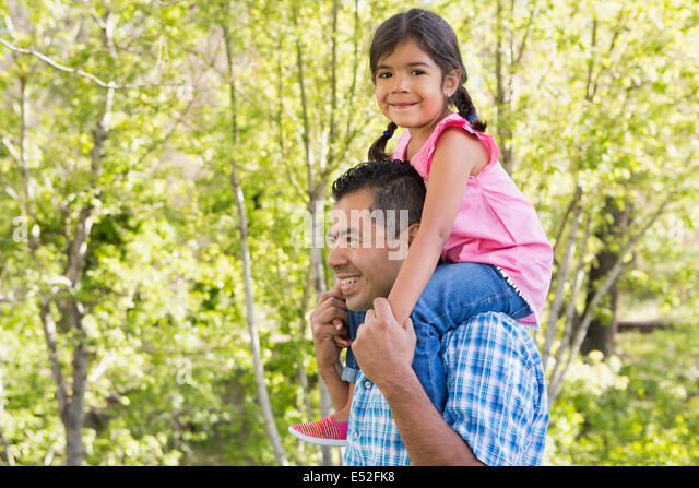 A man giving his daughter a piggyback ride on his shoulders. - Stock Image