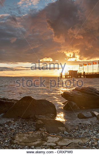 Germany, Nonnenhorn, View of jetty with lake and rocks at sunset - Stock Image